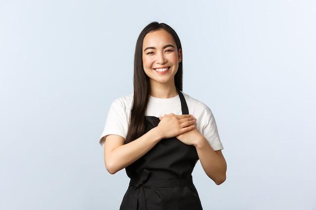 コーヒーショップ、中小企業、スタートアップのコンセプト。素敵な陽気なアジアの女性カフェスタッフ、笑顔の黒いエプロンのバリスタ、クライアントの世話として心に触れる、感謝の気持ちを表す、働くレストランが好き
