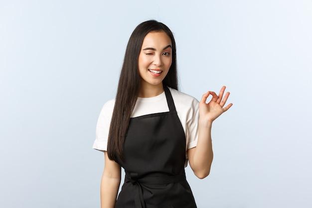 커피숍, 중소기업 및 시작 개념. 건방지고 자신감 있는 아시아 여성 바리스타는 고객에게 ok 사인과 윙크를 보여주고, 문제없다고 말하고, 모든 것을 통제하고, 새로운 음료를 추천합니다.