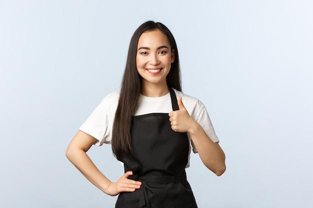 コーヒーショップ、中小企業、スタートアップのコンセプト。黒のエプロンで笑顔のフレンドリーなアジアのウェイトレスは親指を立てます。かわいいバリスタは彼女のカフェで最高品質の飲み物を保証します