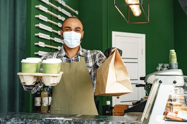食堂のカウンターに立って医療マスクを着用したコーヒーショップの労働者