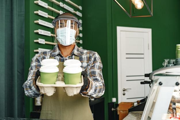 食堂のカウンターに立って医療用マスクを着用した喫茶店員