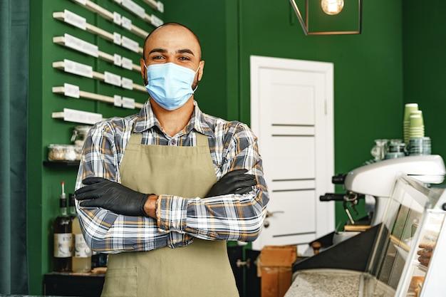 카페테리아 카운터에 서있는 동안 의료 마스크를 쓰고 커피 숍 노동자
