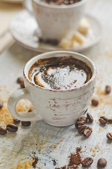 Coffee in a small cup with cane brown sugar and lump sugar on gray wooden table