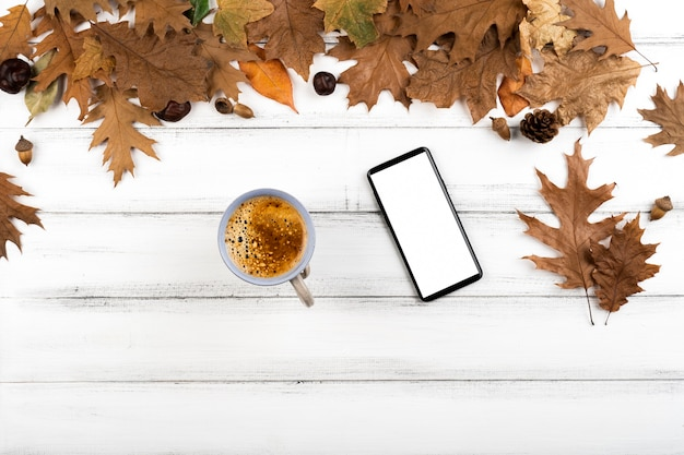 Coffee and smartphone layout on leaves background
