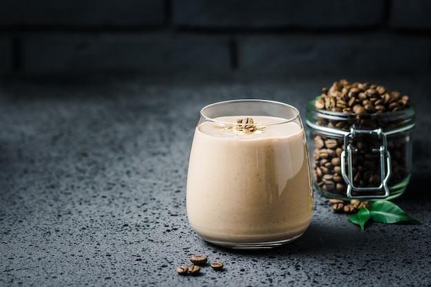 Coffee smoothie and coffee beans in glass jar on dark concrete table