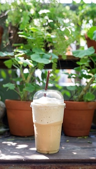 Coffee smoothie on a wooden table and plant background.