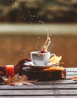 Coffee splash outdoor. autumn composition outdoor. autumn. a cup of hot coffee outdoor.
