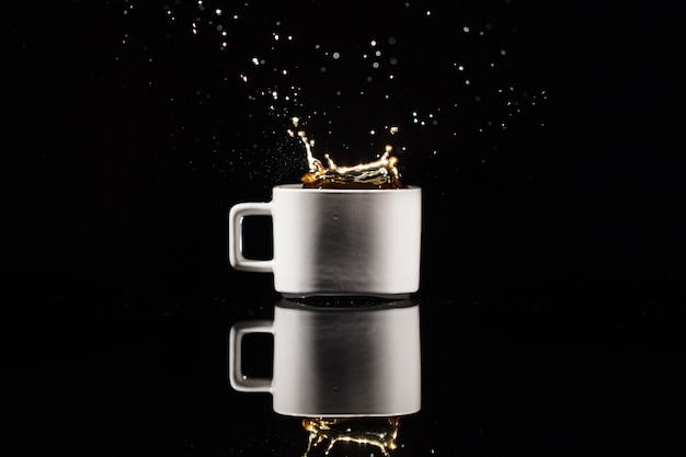 Coffee splashes in white cup on black background