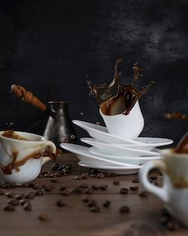 Кофе, плещущийся из чашек на деревянном столе и черном фоне.