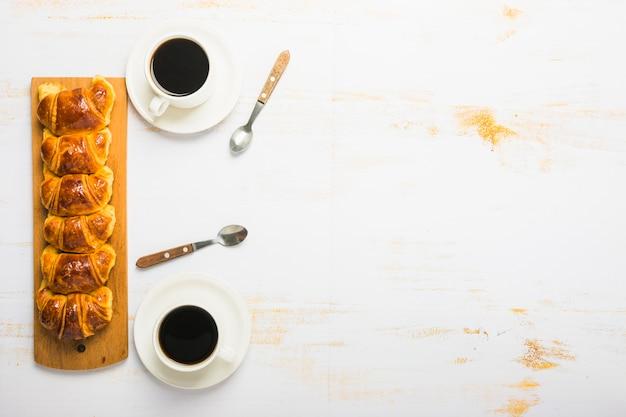 Caffè e cucchiai vicino ai croissant