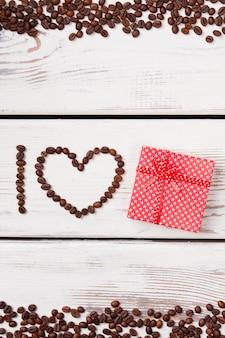 Концепция кофе-сюрприз. форма сердца из коричневых жареных кофейных зерен на белой древесине.
