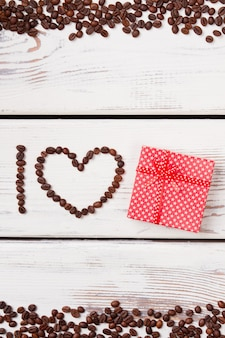 Coffee surprise concept. heart shape from brown roasted coffee beans on white wood.
