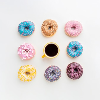 Coffee surrounded by assorted donuts