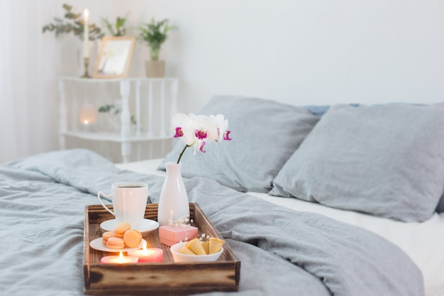 Coffee, sweets,  candles, flowers and girt on wooden tray on bed. concept with valentines day