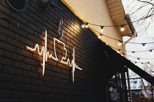 Garlands와 검은 벽돌 벽에 커피 기호입니다.
