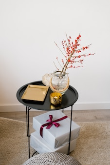 A coffee table with a gold tray, branches with red berries in a glass vase and gift boxes with ribbons and a bow on it