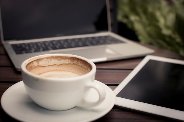 Coffee on table with laptop working in cafe, relax and free time concept