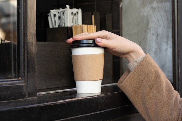 Coffee take away at cafe shop. close up female hand taking paper cup of hot coffee