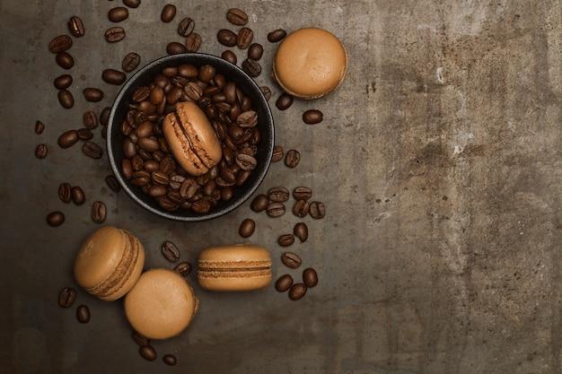 コピースペースのある上面図の暗い金属製のテーブルにコーヒー豆とコーヒー味のマカロン