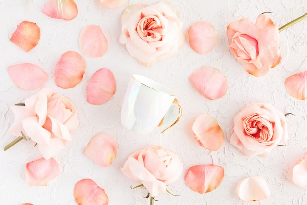 Coffee or tea cup on flowers and petals