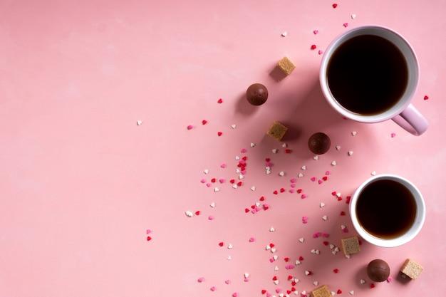 コーヒーティーカップ、ピンクのハートの背景にスイーツキャンディーチョコレート。バレンタインデー142月の最小限の概念。フラットレイ、上、上面図、コピースペース