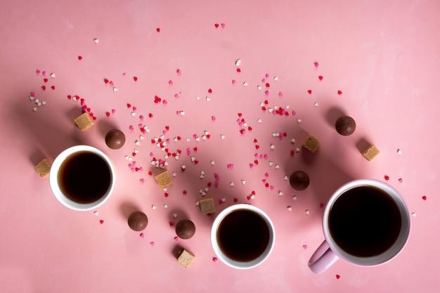 コーヒーティーカップ、ピンクのハートの背景にスイーツキャンディーチョコレート。バレンタインデー142月の最小限の概念。フラットレイ、上、上面図