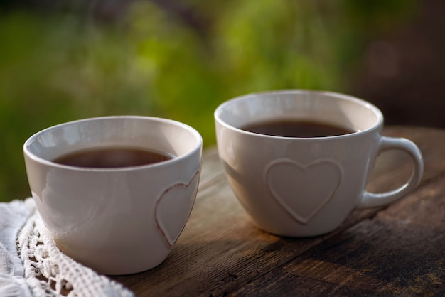 コーヒー、ハートの装飾が施されたカップのお茶、木製のテーブルにレースナプキン。屋外ブランチの軽食。