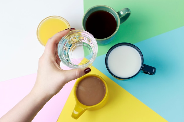 Coffee tea and other drinks in colorful cups on white