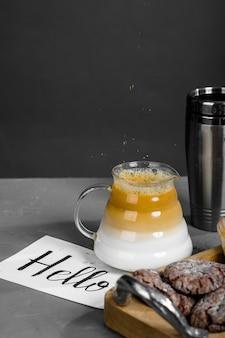 コーヒー、長い注ぎ口のあるティーポット、お菓子、そしてこんにちはの碑文が書かれたカード。