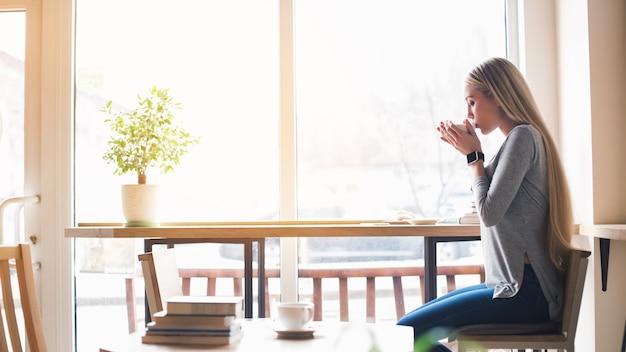 Перерыв на кофе. красивая молодая женщина в кафе с большим окном. женщина пьет кофе и смотрит в окно