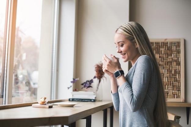 Перерыв на кофе. красивая молодая женщина в кафе с большим окном. женщина с кофе и улыбается