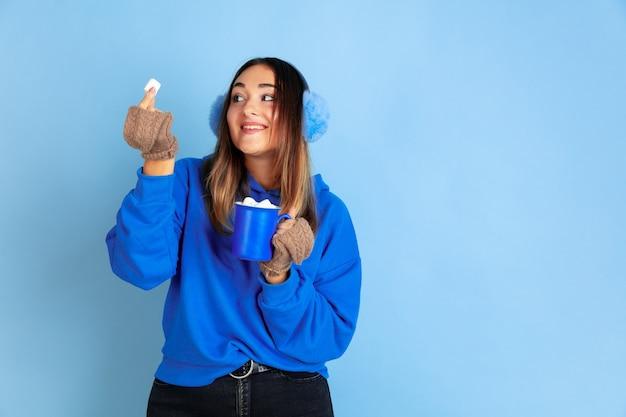 Tempo del caffè. ritratto della donna caucasica su sfondo blu studio. bello modello femminile in vestiti caldi. concetto di emozioni, espressione facciale, vendite, annuncio. atmosfera invernale, periodo natalizio, vacanze.