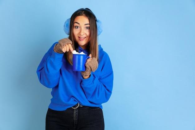 コーヒータイム。青いスタジオの背景に白人女性の肖像画。暖かい服を着た美しい女性モデル。感情、表情、販売、広告の概念。冬の気分、クリスマスの時期、休日。