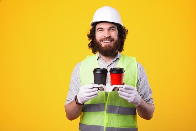 最高の作業チームのためのコーヒータイム。ヘルメットをかぶって、コーヒーを2杯持って行く陽気なひげを生やしたエンジニア