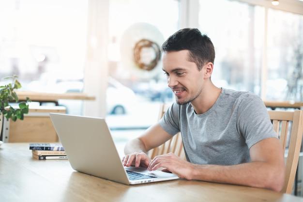 Перерыв на кофе. красивый молодой человек в кафе с большим окном. человек, использующий ноутбук и улыбается