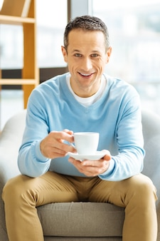 Coffee time. joyful happy nice man sitting in the armchair and looking at you while having a drink
