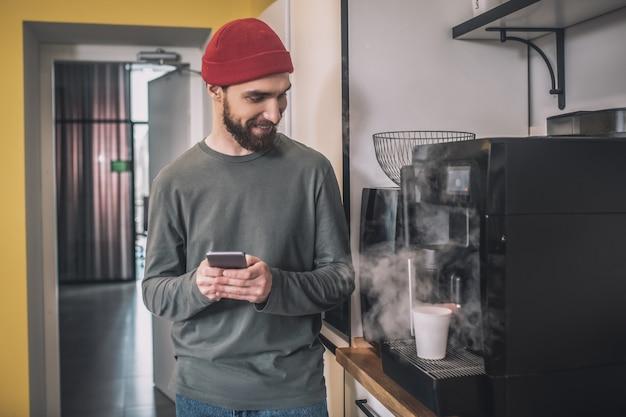 커피 타임. 커피 기계 근처에 서있는 빨간 모자에있는 남자
