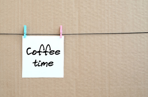 Coffee time. note is written on a white sticker that hangs with a clothespin on a rope on a background of brown cardboard