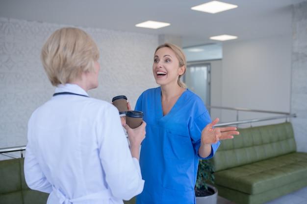 コーヒータイム。コーヒーを飲み、笑い、話している2人の女性医師