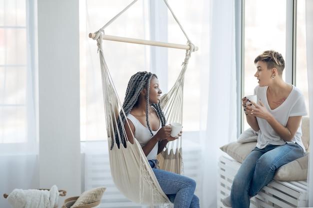 Перерыв на кофе. две девушки пьют кофе в светлой комнате и разговаривают