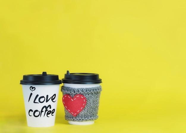 コーヒータイム。黄色の背景に2つの紙のコーヒーカップ。