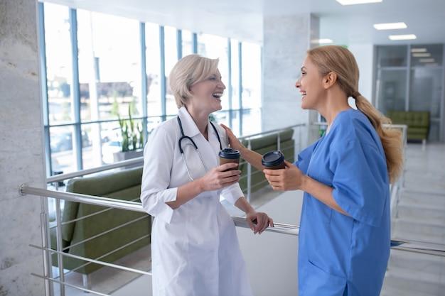 コーヒータイム。階段の手すりに寄りかかって、コーヒーを飲みながら、2人の笑顔の女性医療従事者