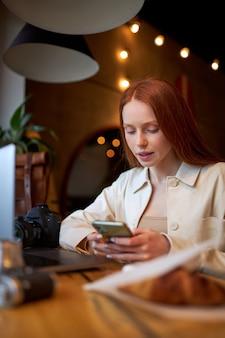 コーヒータイム、カフェで携帯電話とラップトップを使用している女性、働いています。テーブルの後ろに座って、テーブルの上のクロワッサンカジュアルな服装でかわいい赤毛の女性の側面図の肖像画