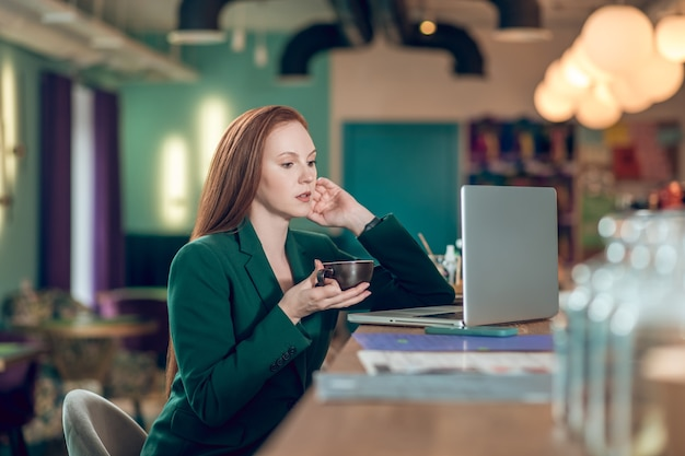 Coffee time. young serious long-haired woman in business green suit drinking coffee while sitting in front of laptop in cafe