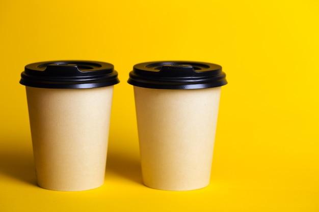 갈 커피. 노란색 배경에 커피와 함께 종이 컵.