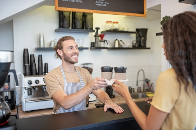 갈 커피. 긴 머리 여자에게 두 커피를주는 커피 숍에서 카운터 뒤에 서있는 정중 한 젊은 수염 바리 스타 남자