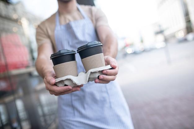 Кофе с собой. два стакана кофе на подставке в вытянутых мужских руках, лица не видно