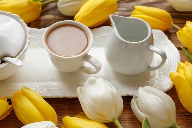 Поднос для кофе между белыми и желтыми тюльпанами на деревянном столе крупным планом