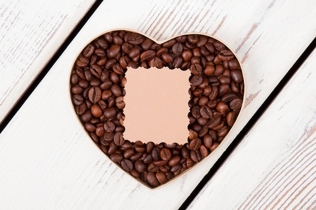 Coffee for valentines day. coffee beans arranged in a heart form and blank paper for copyspace.