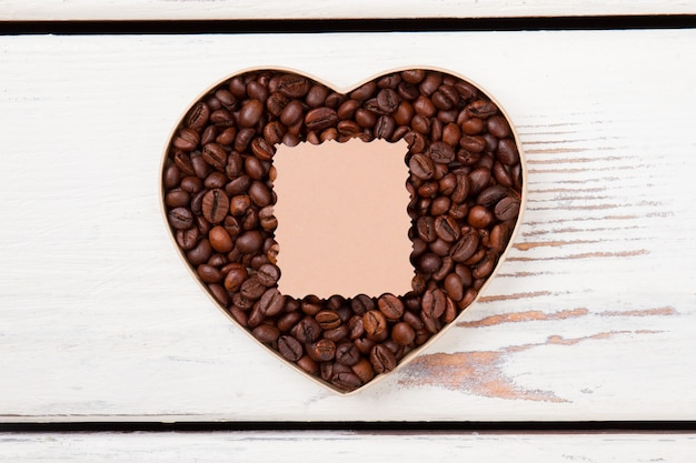 Coffee and valentines day concept. blank beige paper lying over coffee beans arranged in a heart form. copyspace for your text.